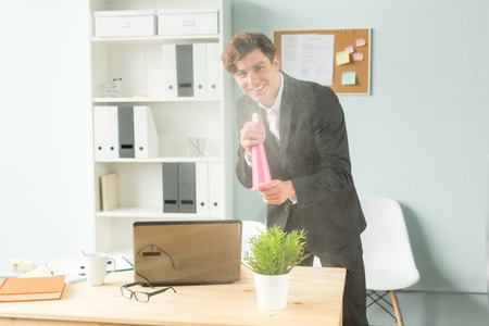 Office, humor, joke and business people concept - handsome man working in office, watering potted plant
