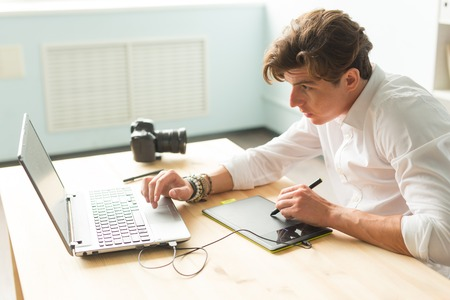 Business, technology, people concept - handsome man working with graphic tablet. He is an architector or multiplicator or designer