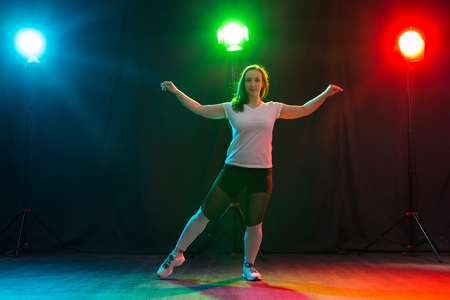 Modern dance, sport and people concept - young woman dancing jazz funk in the darkness under colourful light