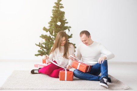 Holidays and Christmas concept - Smiling modern young couple opening Christmas gifts