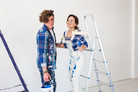 Teamwork and repair concept - young couple doing a renovation in new apartment Imagens