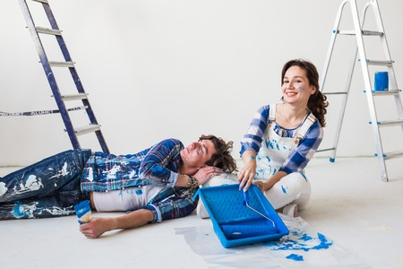 Smiling loving couple doing home renovations. Young woman is holding a paint roller and young man is resting