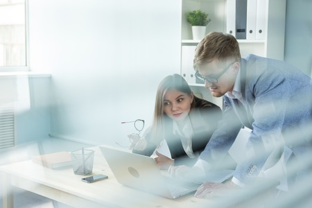 Business and people concept - Portrait of man and woman discussing project in office 写真素材