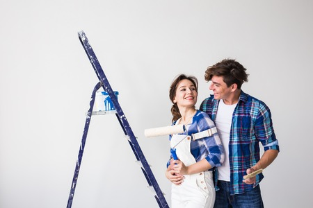 People, redecoration and repair concept - Lovely young couple doing renovation in new apartment