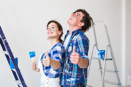 Repair, renovation and love couple concept - young man and woman in love and painting the wall, showing thumbs up Reklamní fotografie