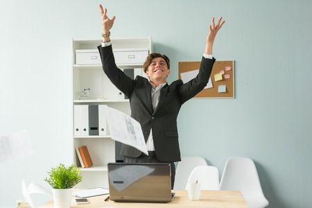 Business people, joke and fun concept - happy funny businessman throwing papers in office
