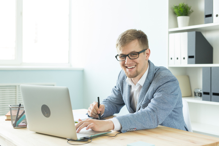 Designer, artist and web design concept - Portrait of young man using digital pen tablet and laptop in the office