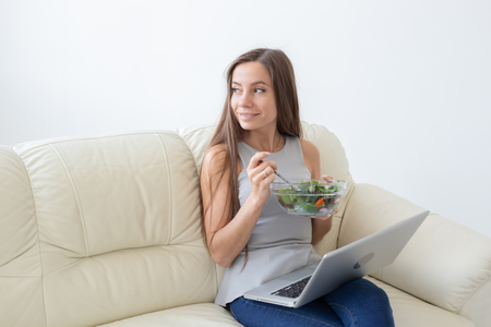 Healthy lifestyle, proper diet, relax and people concept- young beautiful woman sitting on the white sofa and eating a salad Stockfoto