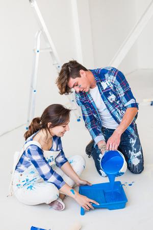 People, renovation and repair concept - portrait of happy couple pour paint