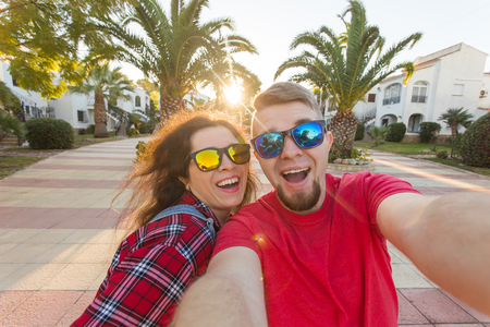 Travel, vacation and holiday concept - Happy couple having fun taking selfie over park with palms background