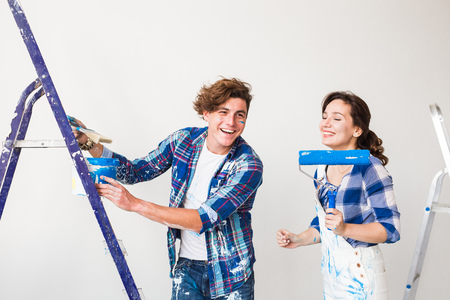 Repair, renovation and love couple concept - young family doing redecoration and painting walls together and laughing.