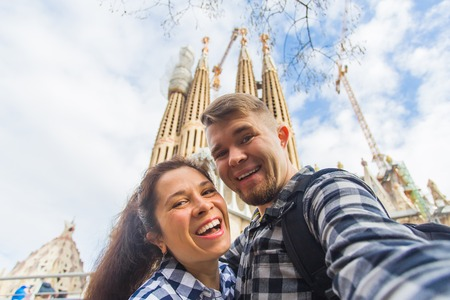 BARCELONA, SPAIN - FEBRUARY 6, 2018: Happy couple making selfie photo in front of the famous Sagrada Familia catholic cathedral. Travel in Barcelona Redakční