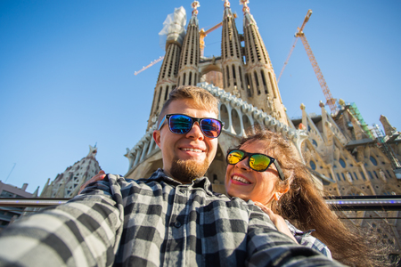 BARCELONA, SPAIN - FEBRUARY 7, 2018: Happy tourists photographing in front of the famous Sagrada Familia roman catholic church in Barcelona, architect Antoni Gaudi