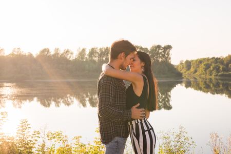 Love, romantic and nature concept - young couple hugging near the lake
