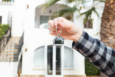Real estate and property concept - Hand is holding house keys on house shaped keychain in front of a new home Standard-Bild