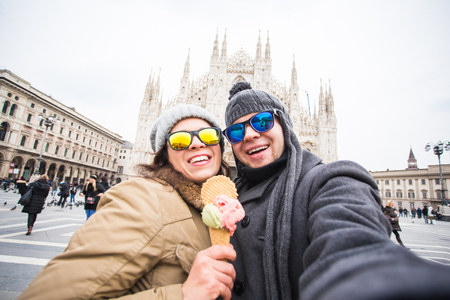Travel in winter and Italy concept - Happy young couple take selfie photo with ice-cream in front of Milan Duomo Cathedral. Banque d'images