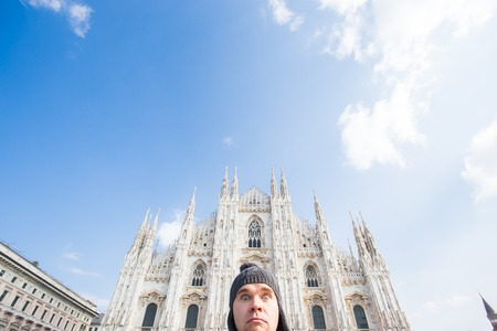 Italy, excursion and travel concept - funny guy taking selfie in front of cathedral Duomo in Milan 스톡 콘텐츠