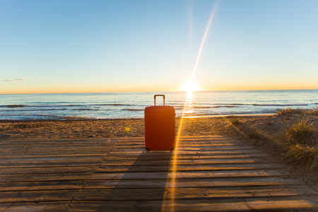 Luggage, holidays, travel concept - a red suitcase standing near the sea in sunlight