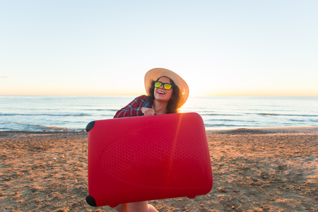 Travel, holiday and vacation concept - Funny young woman holding suitcase on the beach Stock Photo