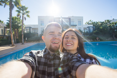 Travel, vacation and holiday concept - Beautiful love couple having fun taking selfie near a swimming pool.