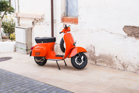 Barcelona, Spain - January 13 , 2018: Orange Scooter Vespa parked on old street in Barcelona, Spain