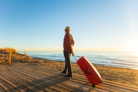 Nature, travel and people concept - Handsome man walking on with red suitcase near the sea and watching to the sunset