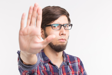 People, expression and gesture concept - young man showing stop gesture on white background Stock Photo