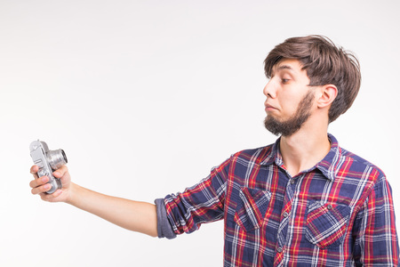 People, photographer and gesture concept - man using an old fashioned camera looking through the lens on white background