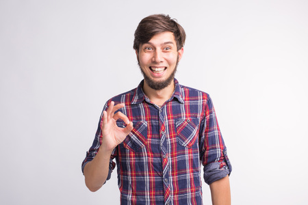 Gestures, signs and people concept - smiling confused man shows okay sign over the white background Banco de Imagens