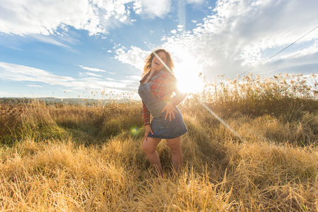 Summer, freedom and holidays concept - Happy woman fooling around in golden wheat