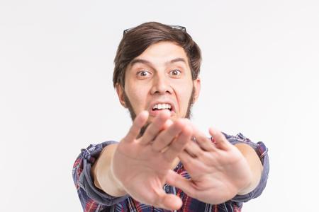 People, expression and gesture concept - young man showing stop gesture on white background Banco de Imagens