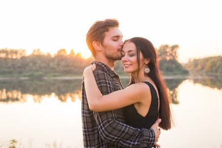 Relationship, love and nature concept - Close up portrait of attractive woman and handsome man hugging on the background of the lake Archivio Fotografico