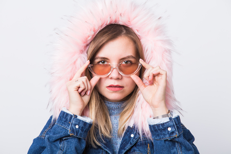 Young fashionable woman in autumn outfit. Denim coat with a hood and pink faux fur Archivio Fotografico
