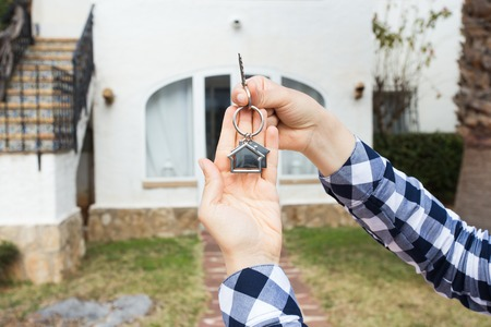 New home, house, property and tenant - Real estate agent handing a house key.