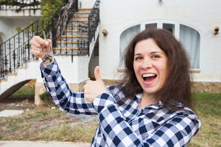 Real estate and property concept - Happy young woman in front of new home with new house keys Banco de Imagens