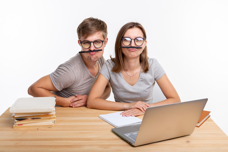 Education and people concept - a couple of young students in glasses look like they are bored of learning homework and make a stupid jokes