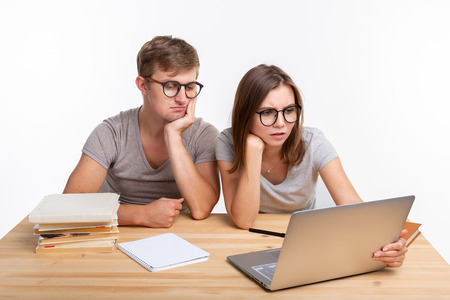Education and people concept - couple of young people in glasses look like they are bored of learning homework