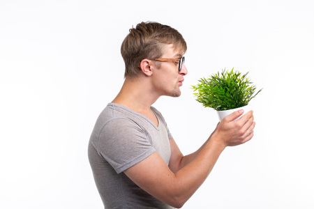 Nature, fun, fool around and nerd concept - Portrait of funny young man kissing a plant over the white background