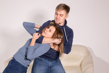 People, abuse and violence concept - aggressive man strangling his wife