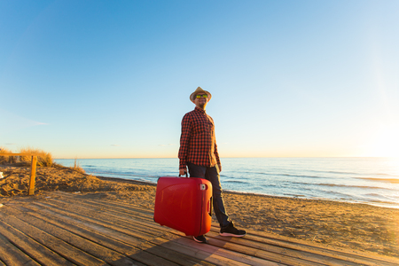 Sea, travel, people concept - a man standing near the sea with red suitcase