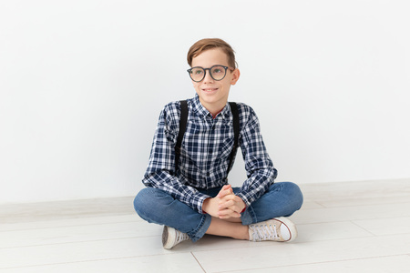 teenager, children and fashion concept - Cute child with glasses sitting on the floor over white background