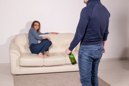alcoholic, domestic violence and abuse concept - man gets drunk at home and takes his anger at his wife Stock Photo