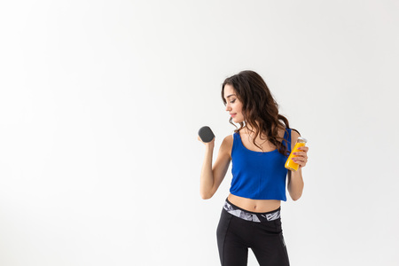 Sport, healthy lifestyle, people concept - young woman holds bottle of juice and a dumbbell on white background with copy space