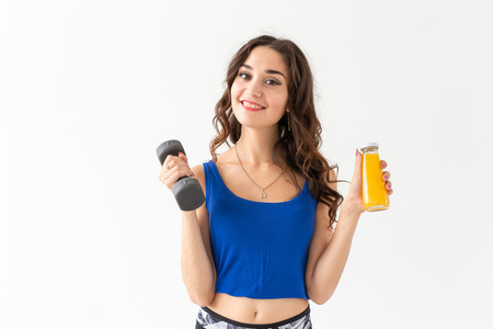 Sport, healthy lifestyle, people concept - close up of young woman with a dumbbell in her hand and a bottle of juice in another hand on white background