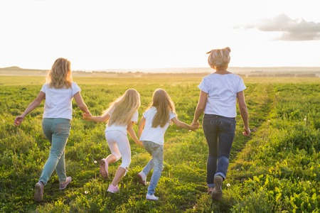 Family, fun and holiday concept - Mothers and her daughters going away in green field Banco de Imagens
