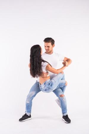 Young couple dancing social dance bachata, merengue, salsa, kizomba. Two elegance pose on white room.