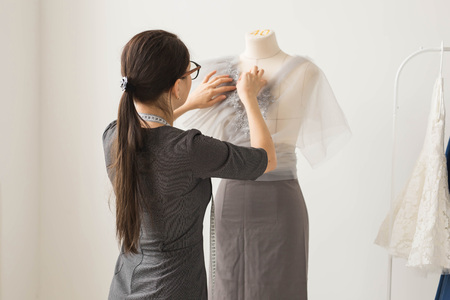 Dressmaker, technologies, fashion designer and tailor concept - young female fashion designer working in her showroom Archivio Fotografico