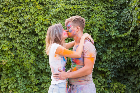Holiday, holi and people concept - Happy couple having fun covered in paint