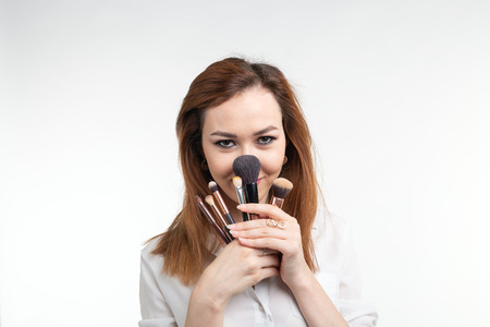 Attractive visagist or korean make-up artist fooling around with makeup brushes on white background Stockfoto