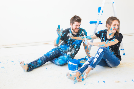 People, renovation and interiors concept - Young couple sitting on the white floor and have fun at the break Stockfoto